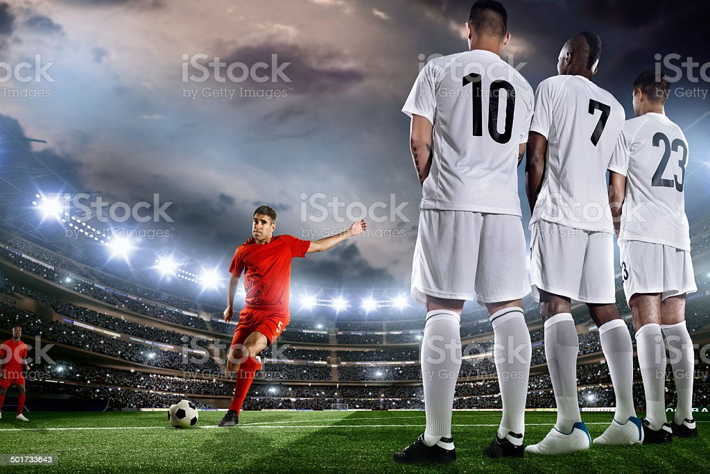 Soccer player kicks a ball in front of wall stock photo