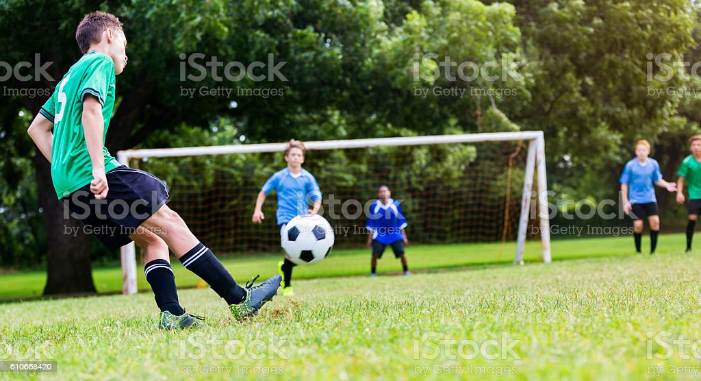 Soccer player kicks ball stock photo