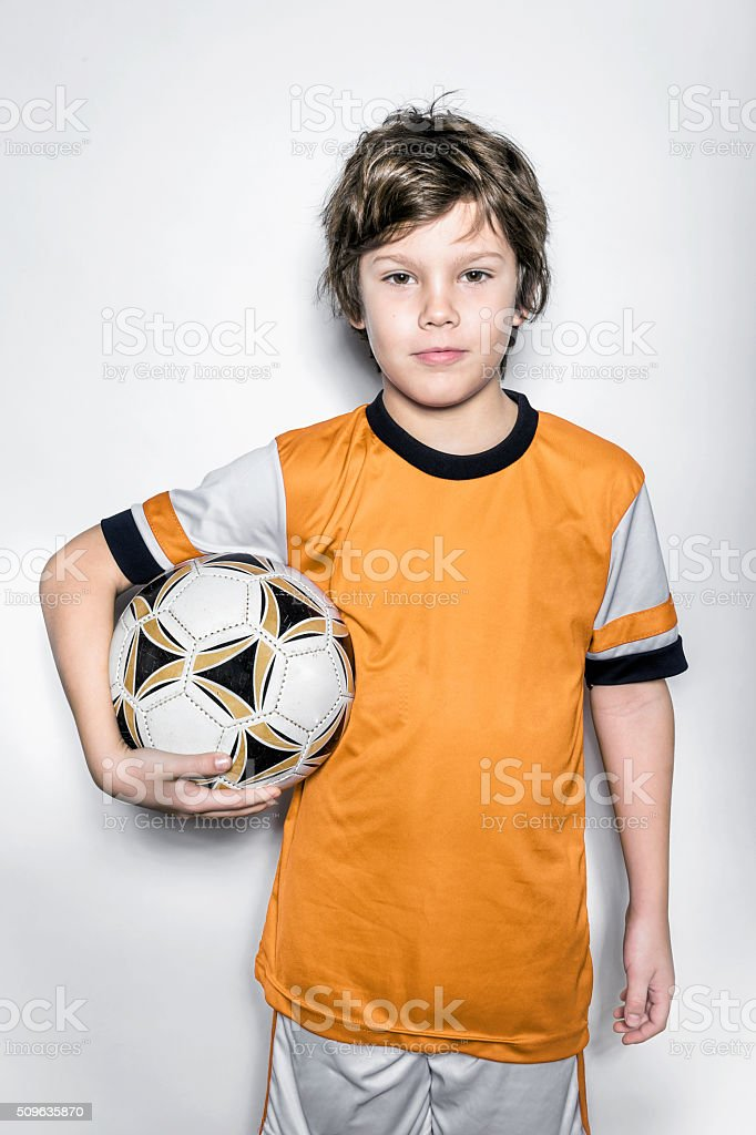 Soccer Player Kid in Orange Uniform With Ball stock photo