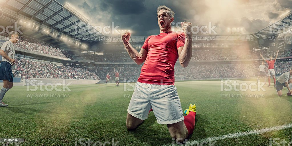 Soccer Player Kneeling on Pitch With Clenched Fists in Celebration stock photo
