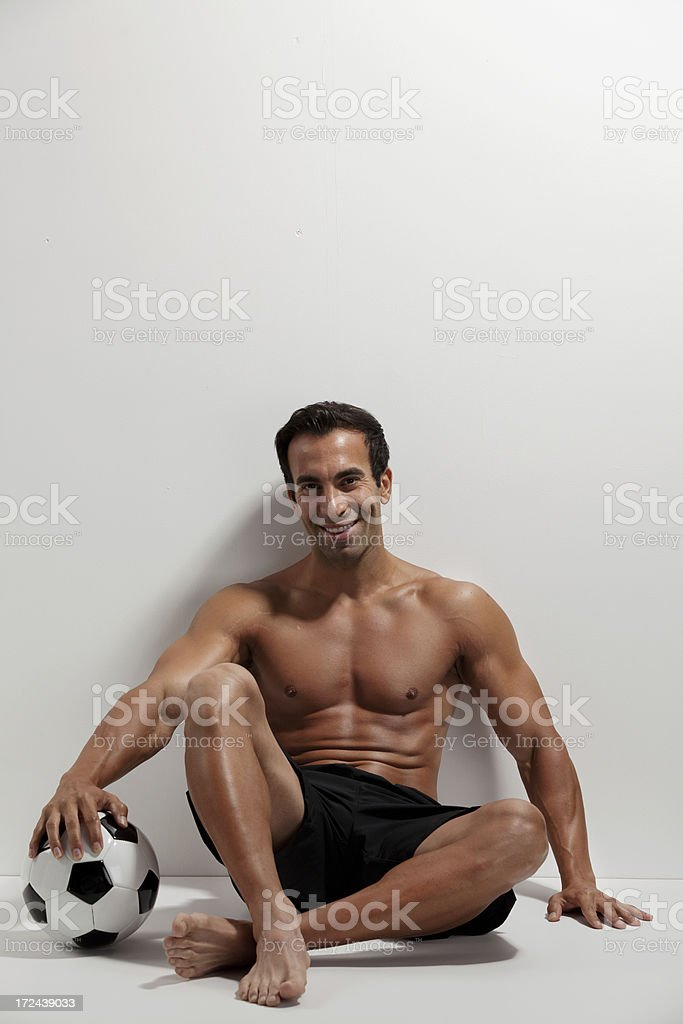 Soccer player leaning against a wall royalty-free stock photo