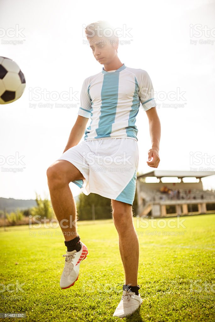 Soccer player playing with soccer ball stock photo
