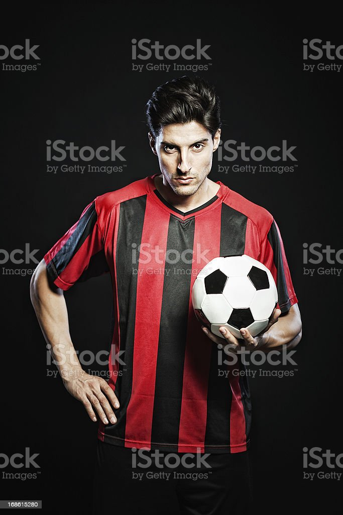 Soccer player portrait on black background, vertical. stock photo