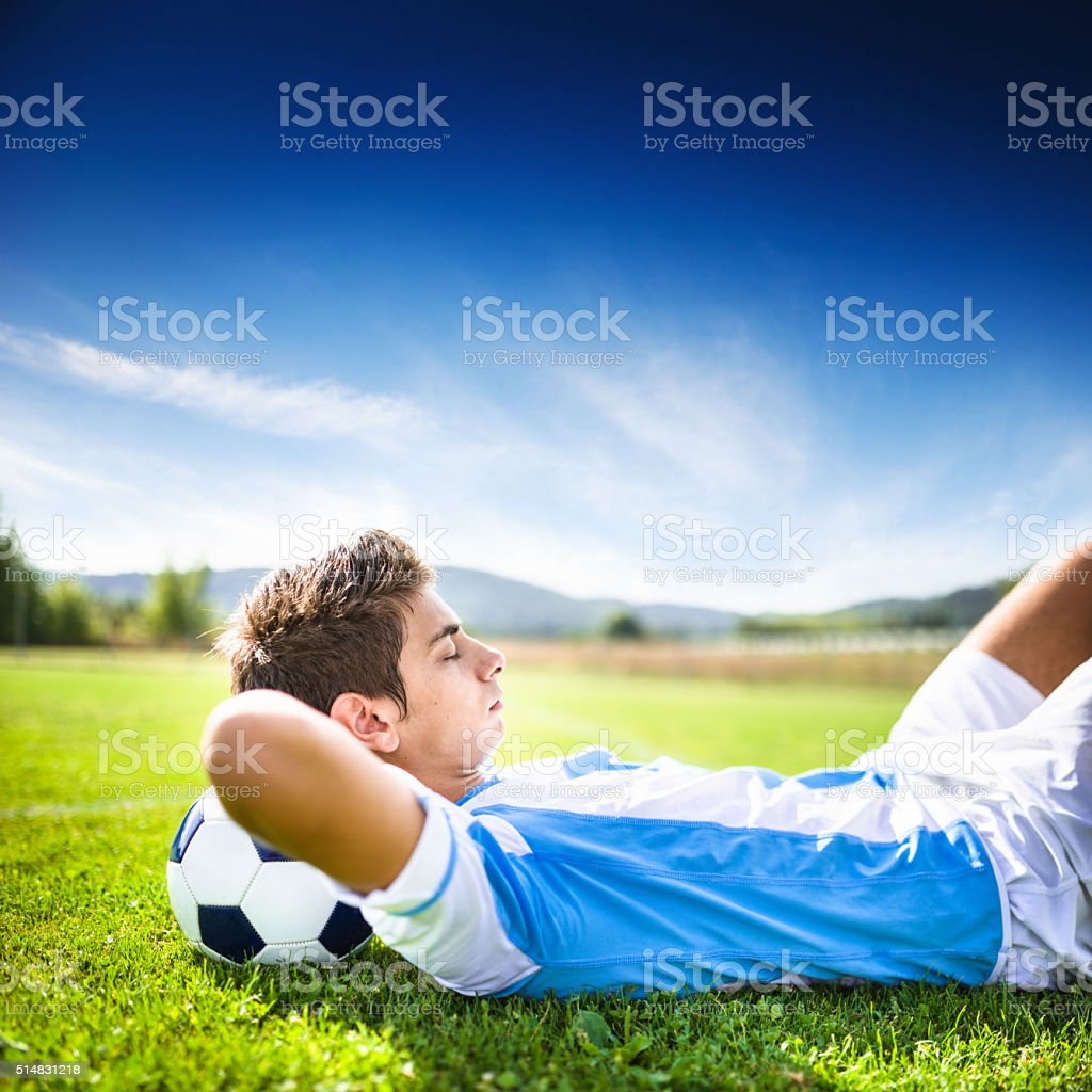 Soccer player relaxing on the pitch stock photo