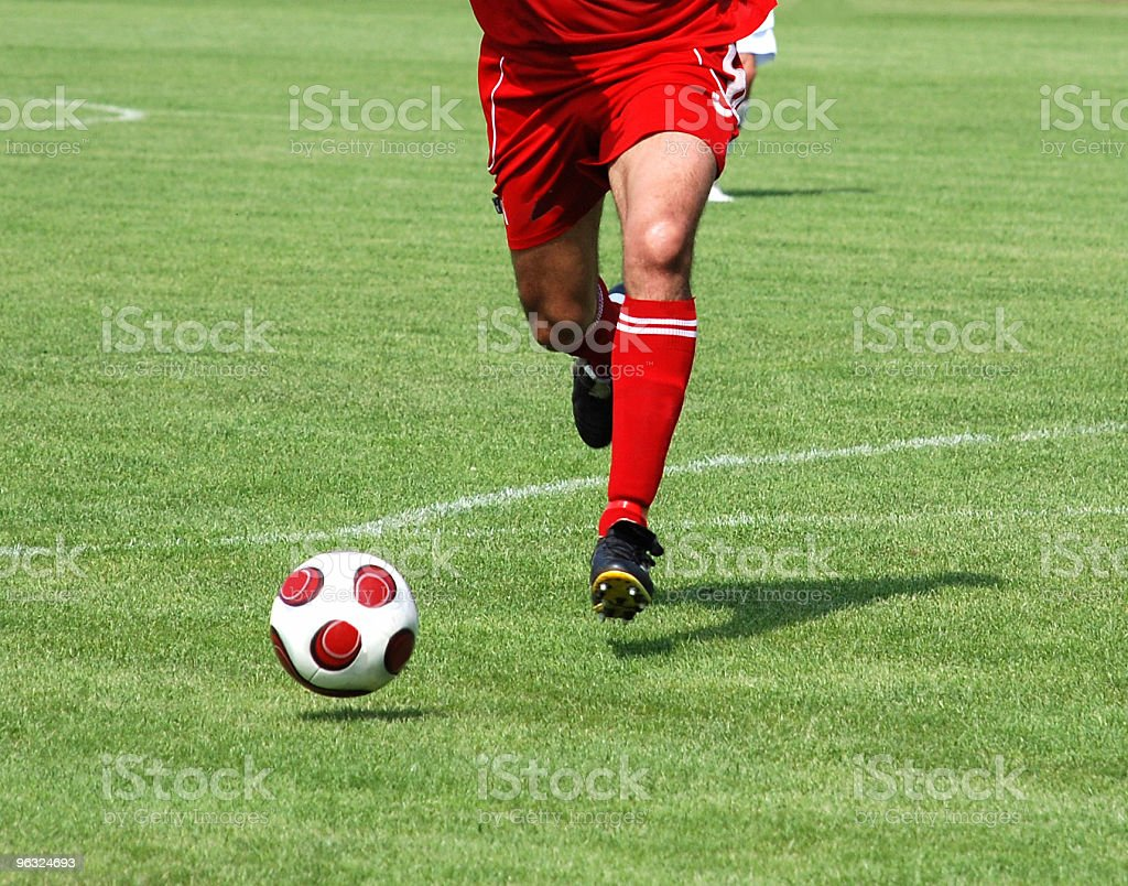 soccer player running after the ball royalty-free stock photo