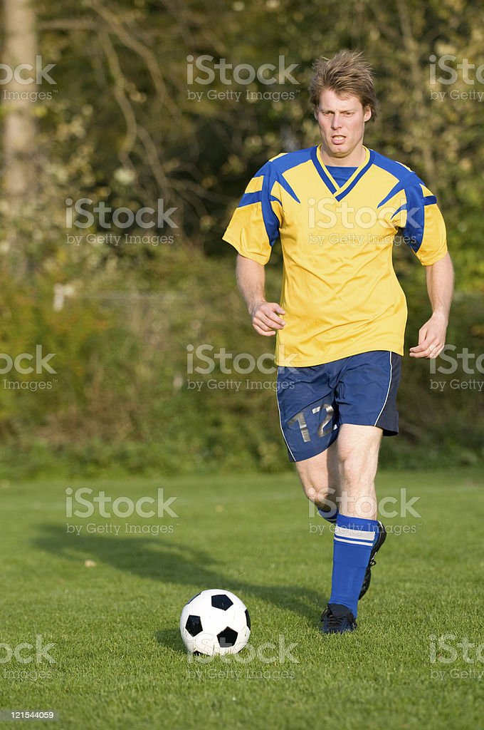 Soccer player runs with ball and looks tired royalty-free stock photo