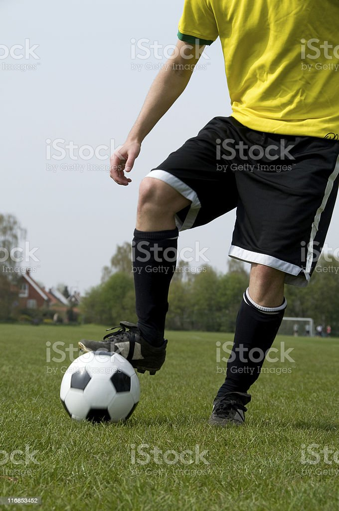 Soccer player runs with ball on a football field royalty-free stock photo