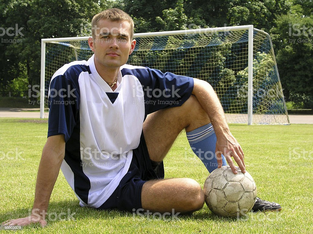 Soccer player sitting on a field royalty-free stock photo