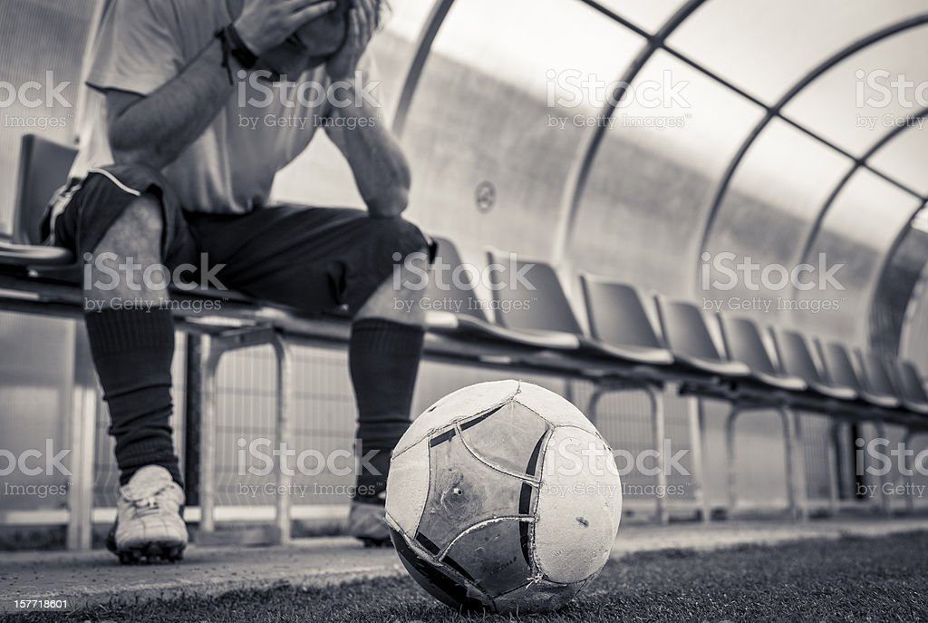 Soccer player sitting on bench royalty-free stock photo
