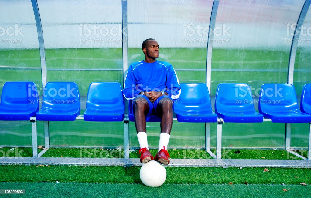 Soccer Player Sitting on Sidelines stock photo