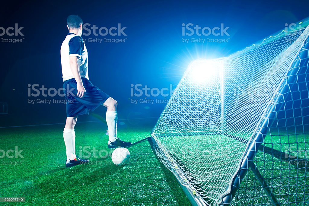 Soccer player stands on a field ready for kick off stock photo