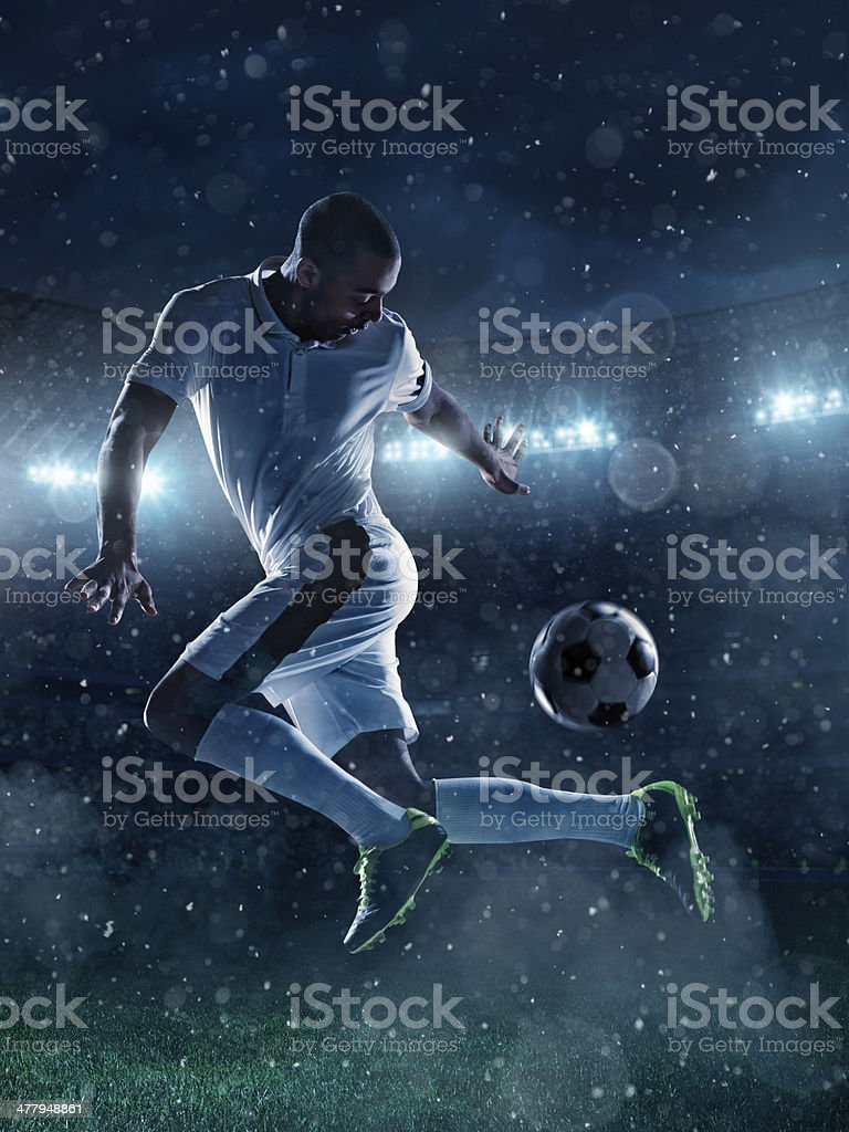 Soccer player tackling a ball on stadium royalty-free stock photo
