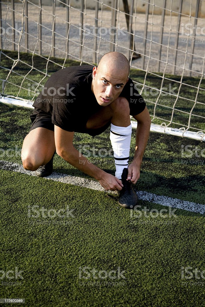 Soccer player tying his shoe royalty-free stock photo
