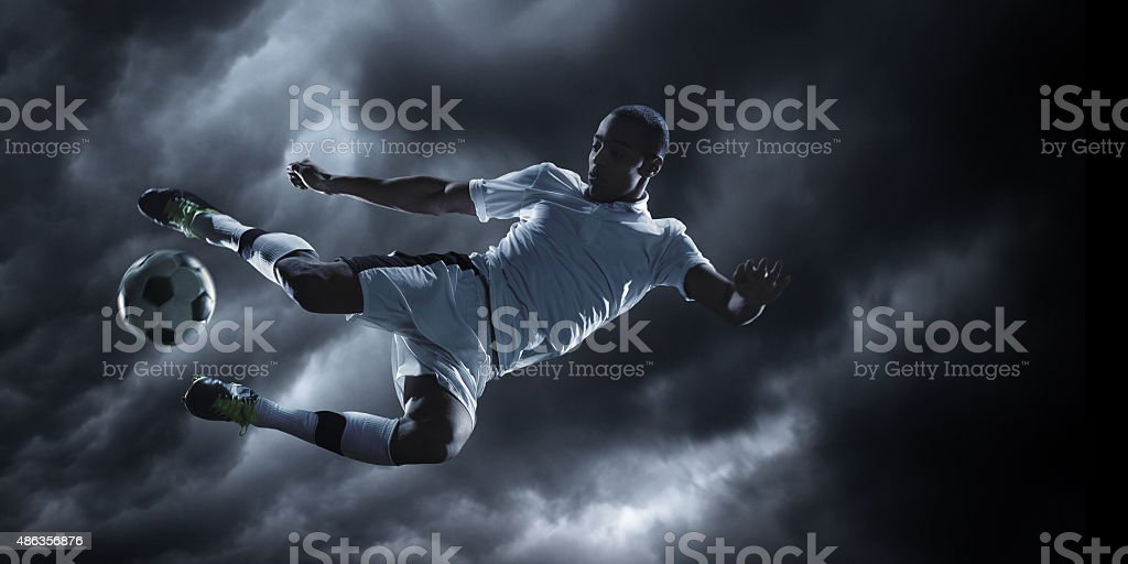 Soccer player under dramatic sky stock photo