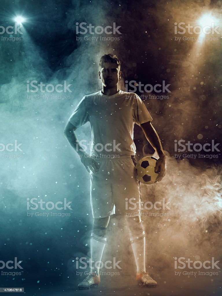 Soccer player with ball standing under two-color spotlights stock photo