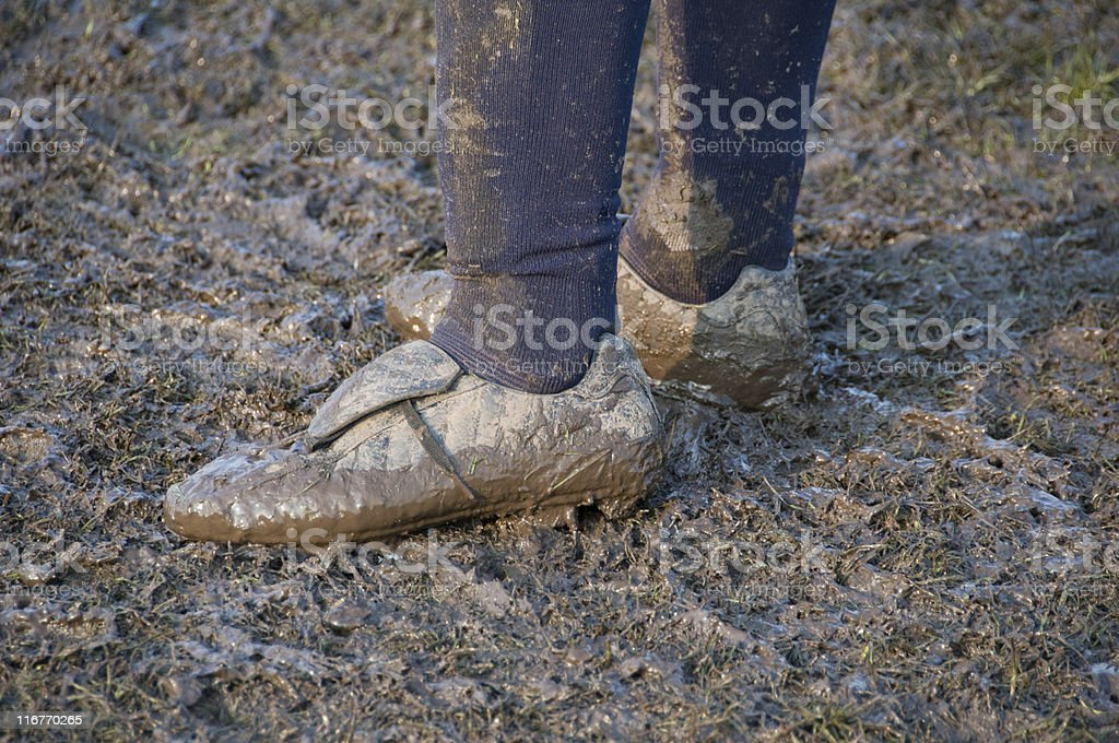 Soccer player with dirty football shoes full of mud royalty-free stock photo