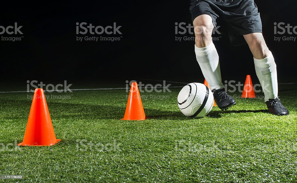 A soccer players feet kicking a ball through cones royalty-free stock photo