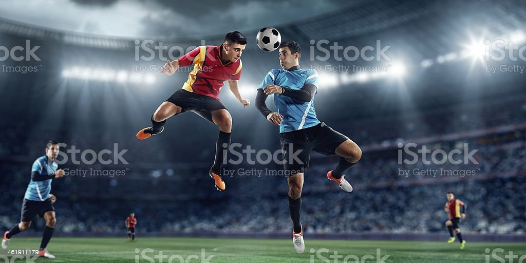 Soccer players fight for ball in midair stock photo
