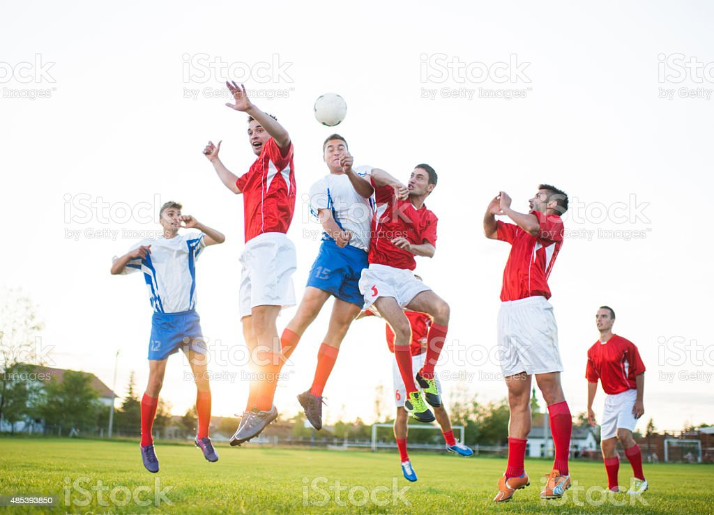 Large group of soccer players jumping to head the ball.