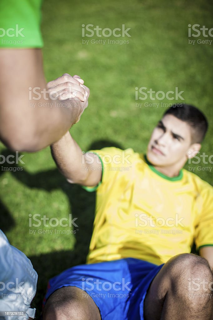 Soccer players helping each other royalty-free stock photo