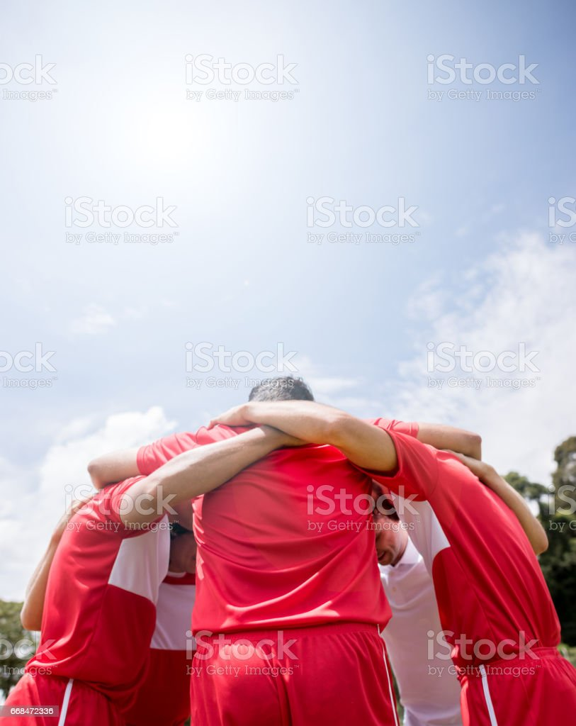 Soccer players hugging and discussing tactics stock photo