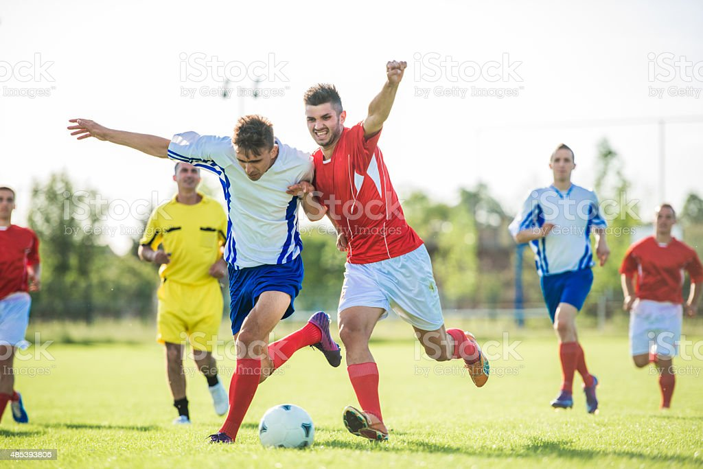 Soccer players in action on a playing field. stock photo