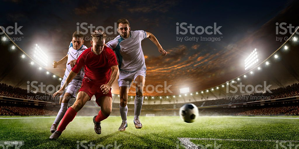 Soccer players in action on sunset stadium background panorama stock photo