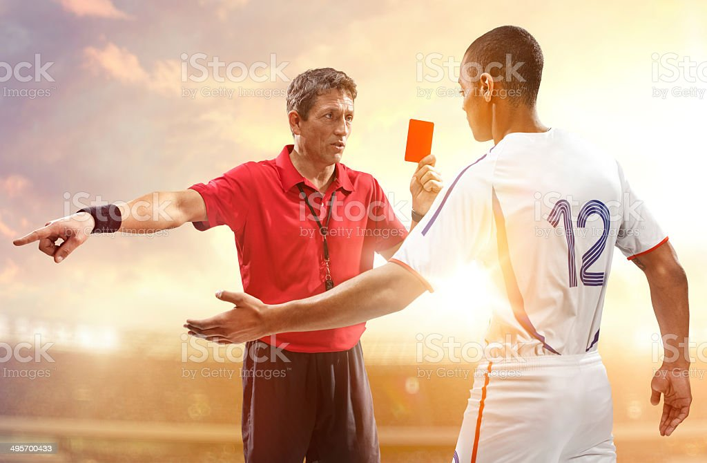 Soccer referee and football player stock photo