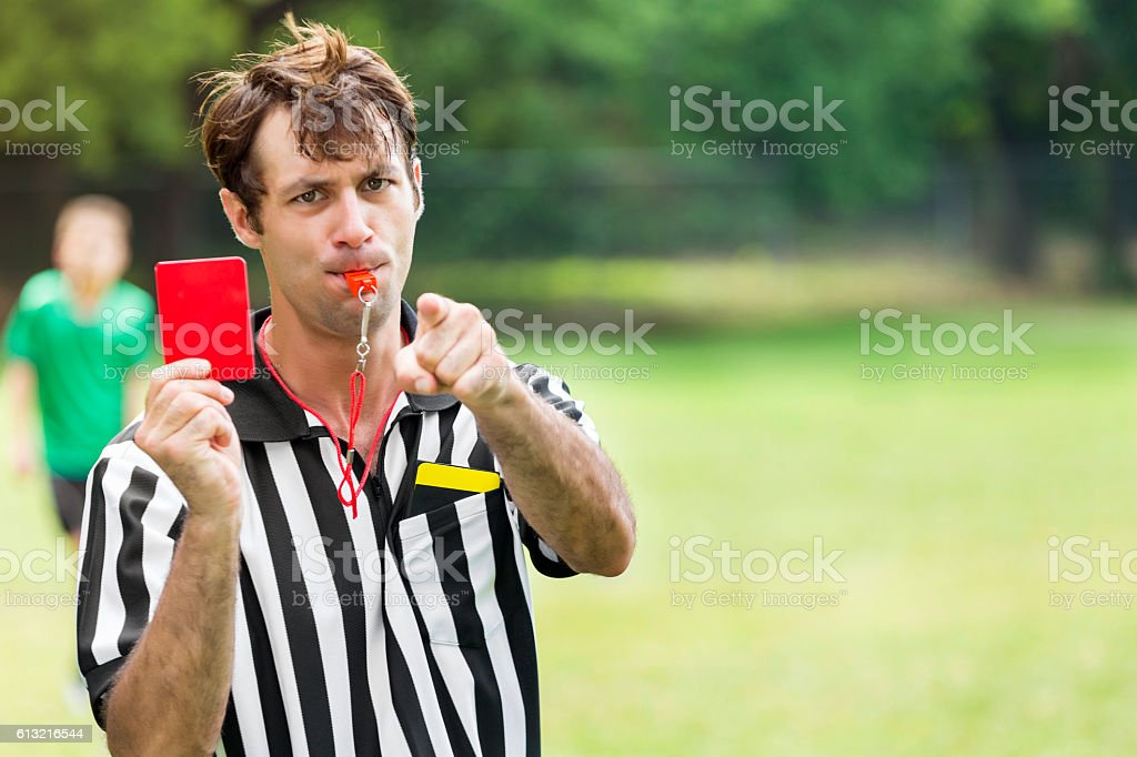 Soccer referee points and holds up red card stock photo