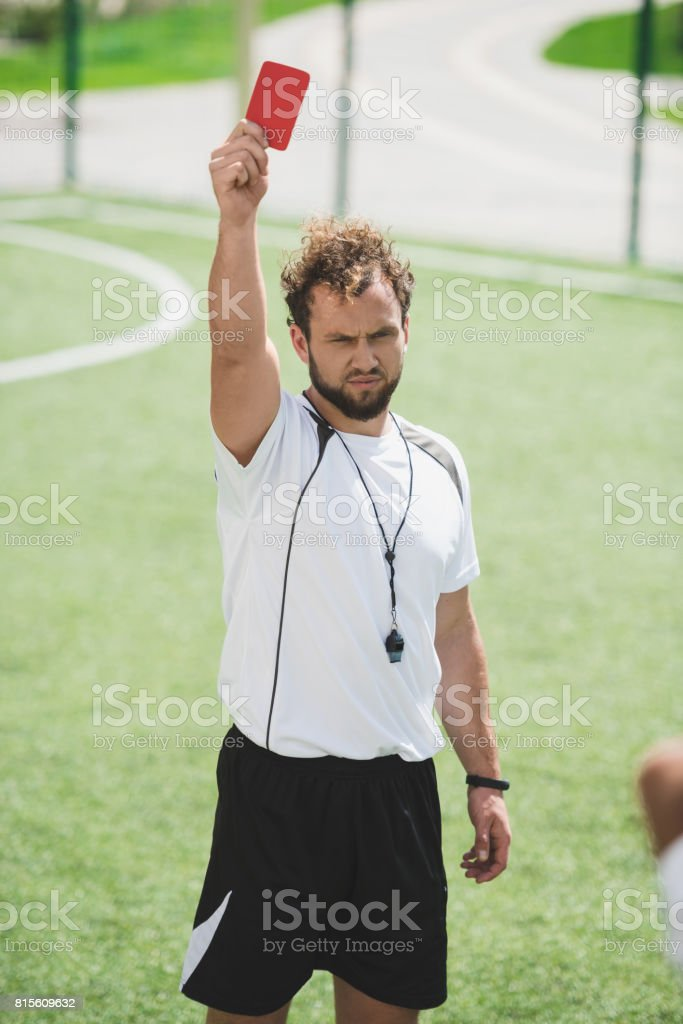 soccer referee showing red card during soccer match on pitch stock photo