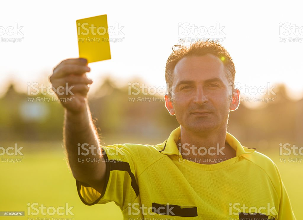 Soccer referee showing yellow card at sunset. stock photo