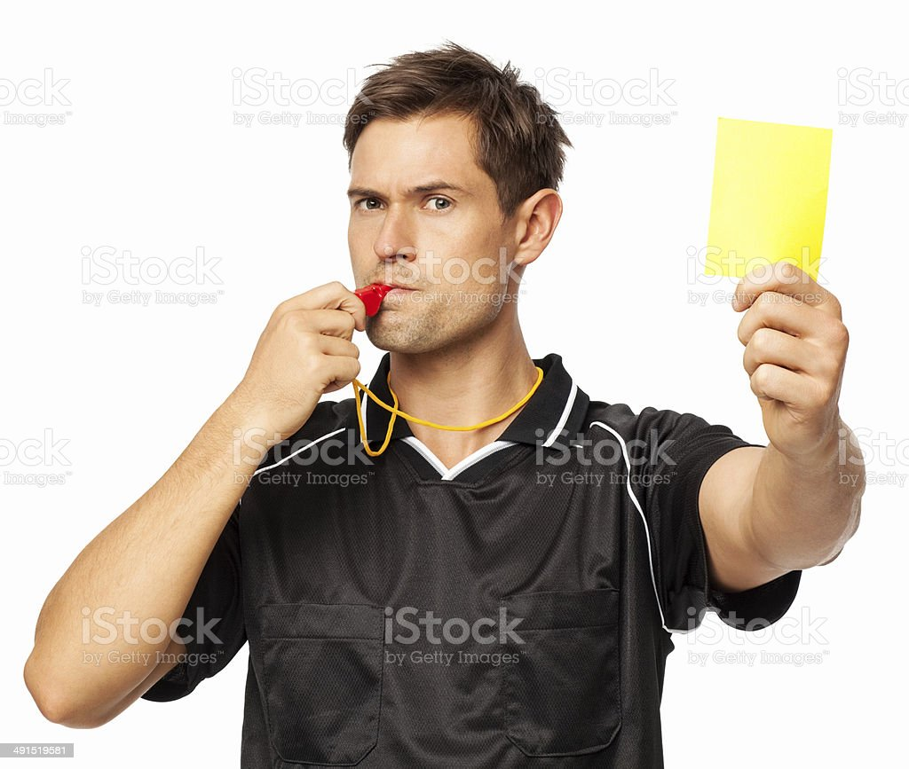Soccer Referee Showing Yellow Card While Whistling stock photo