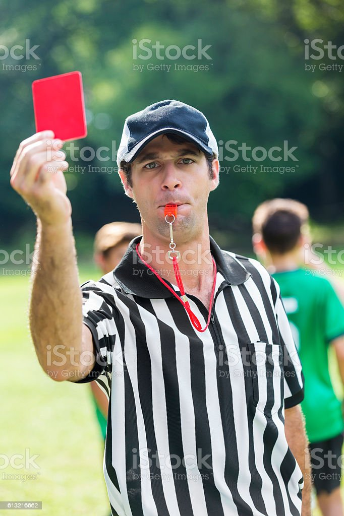 Soccer referee shows a red penalty card while blowing whistle stock photo