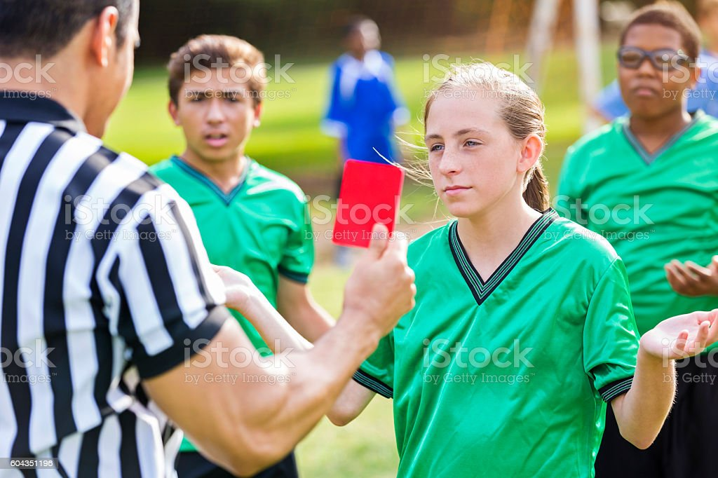 Soccer referee shows red card to female soccer player stock photo