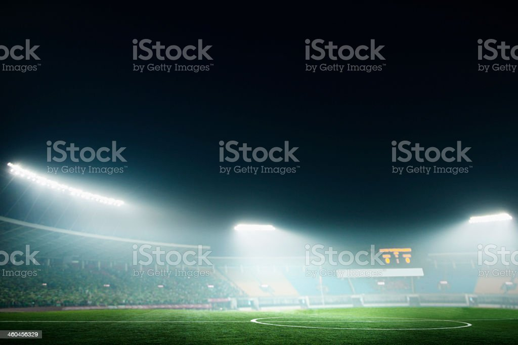 A soccer stadium lit up at night stock photo