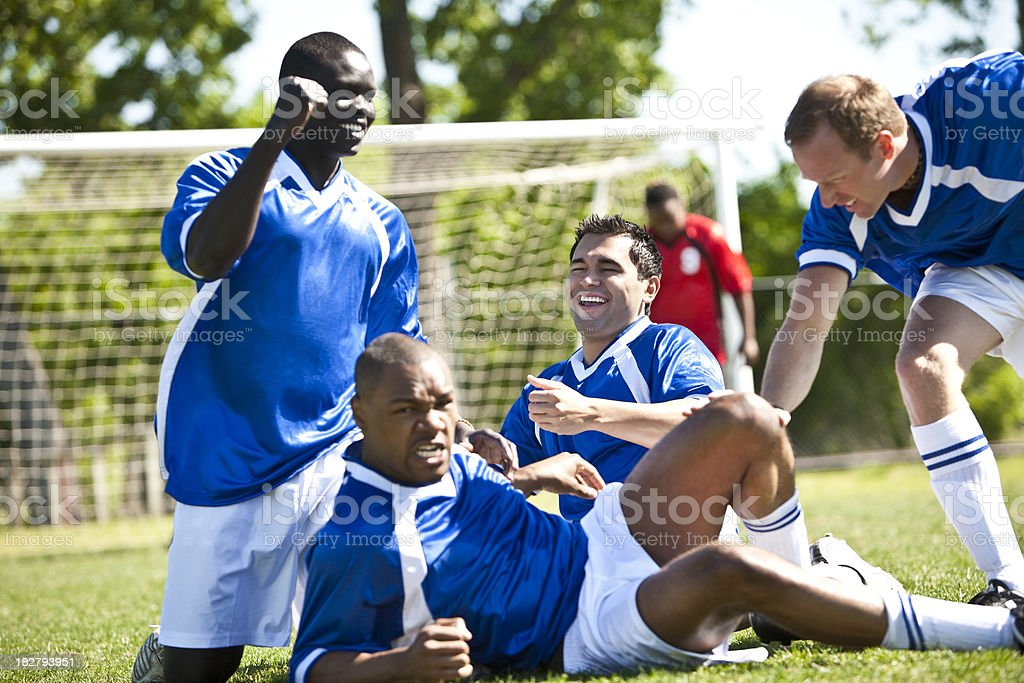 Soccer Team on The Ground Celebrating Their Goal royalty-free stock photo
