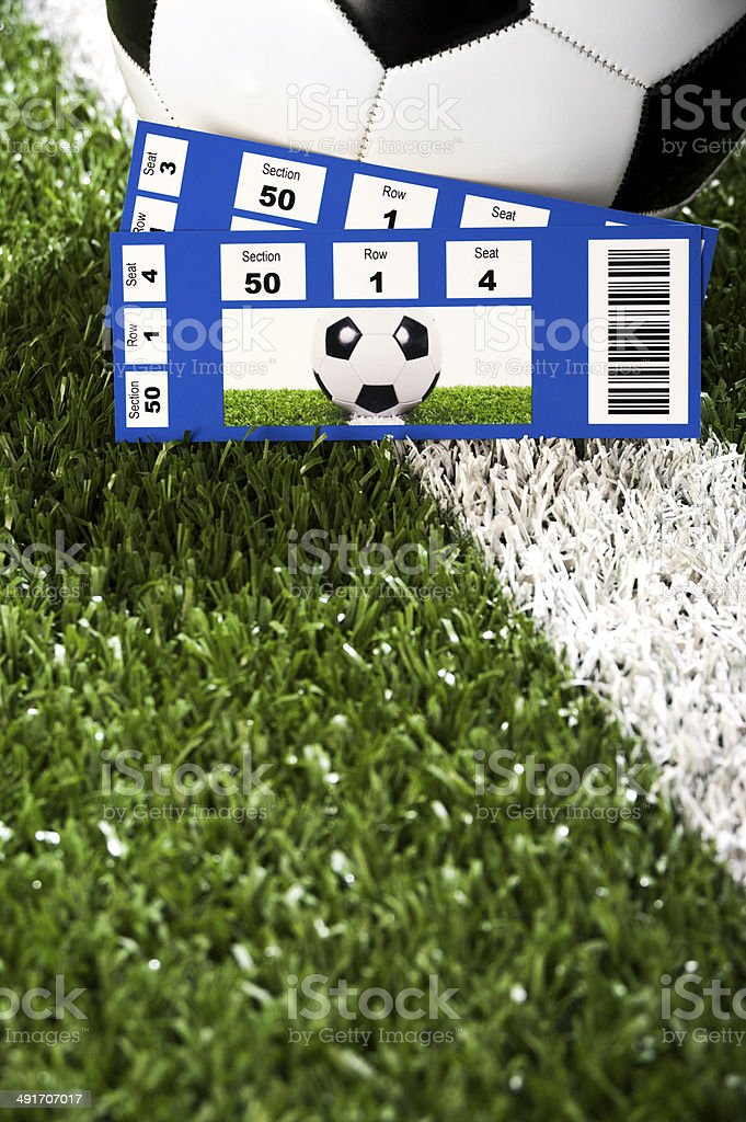 A pair of Tickets Stubs sitting in front of a Soccer Ball on Midfield...
