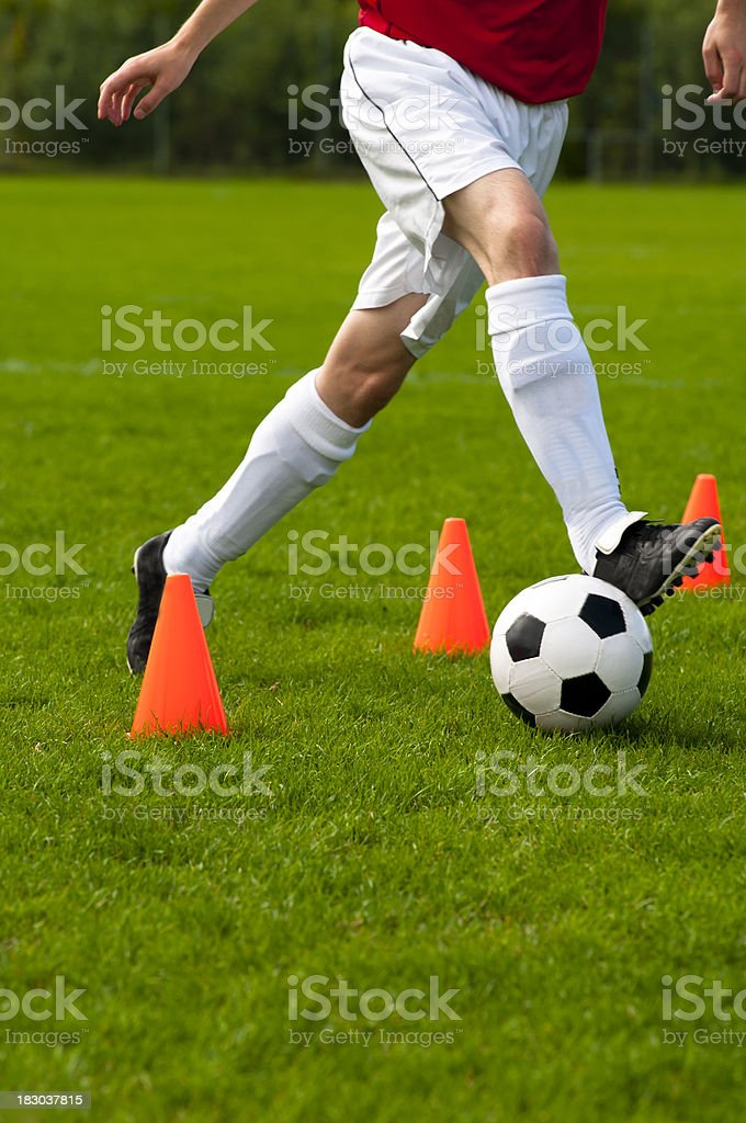 Soccer training and player runs with football past red cones royalty-free stock photo