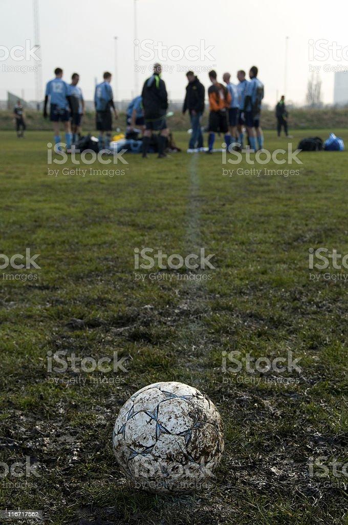 Soccerball on a muddy football field royalty-free stock photo
