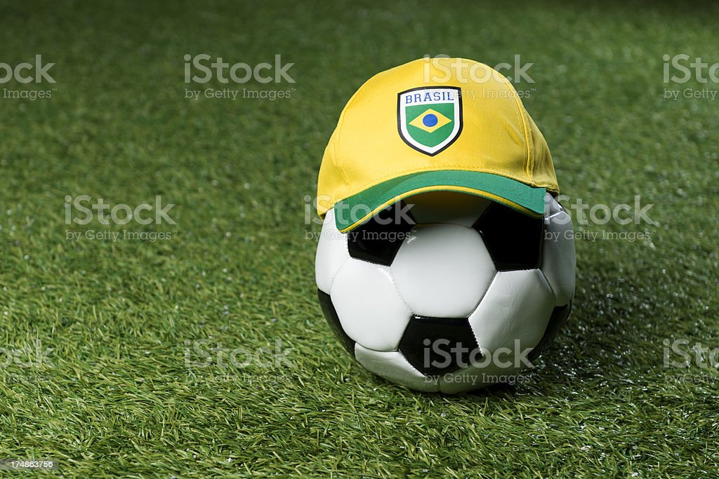 Soccerball on the grass with a cap royalty-free stock photo