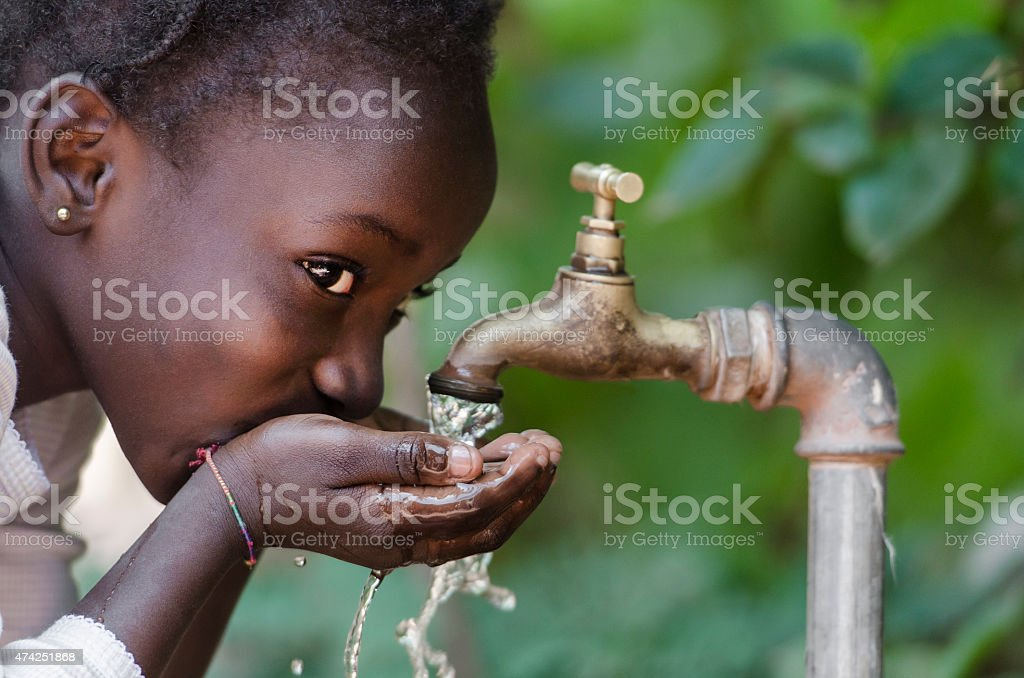 Social Issues: African Black Child Drinking Fresh Water From Tap stock photo
