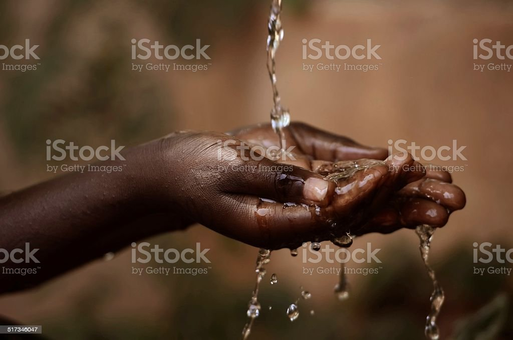 Social Issues: Water Pouring in African Child's Hands stock photo