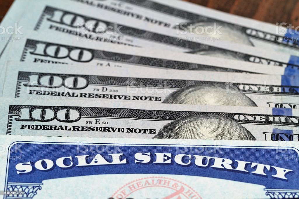 Social security card and USA currency 100 dollar bills stock photo