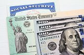Social Security card, Treasury checks and hundred dollar bills