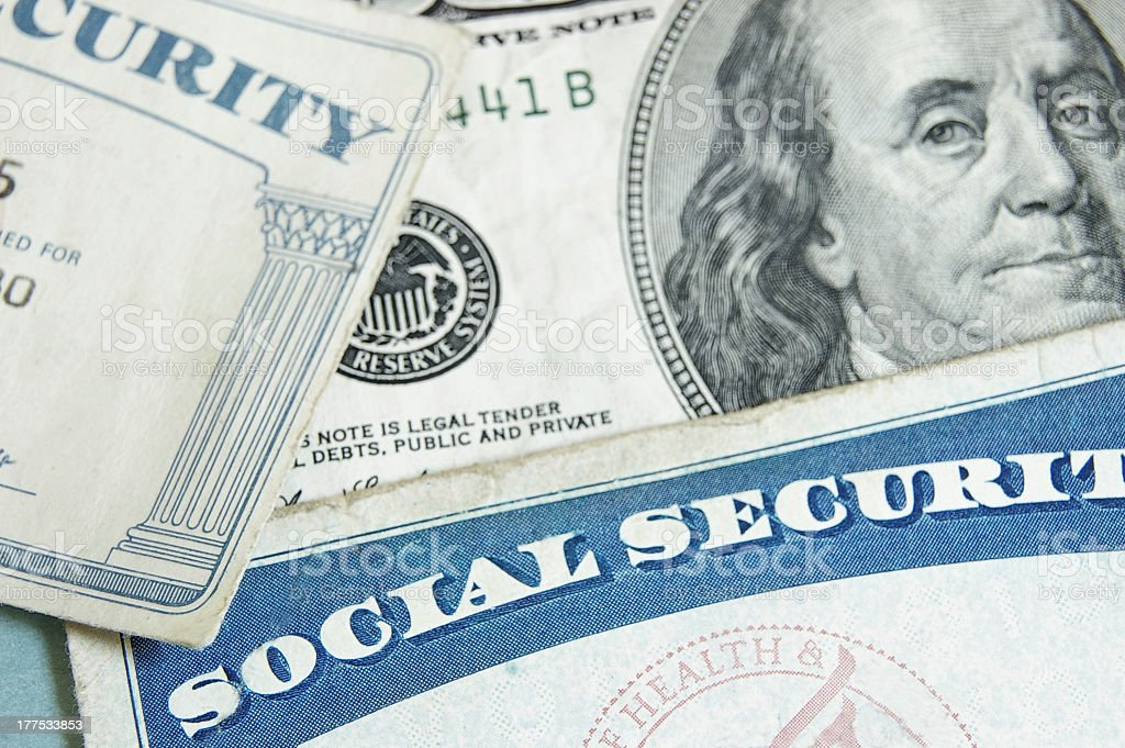 Social security cards angled on top one hundred dollar bill royalty-free stock photo