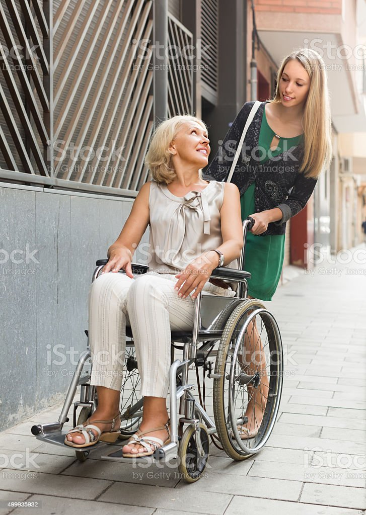 Social worker and disabled woman at stroll stock photo