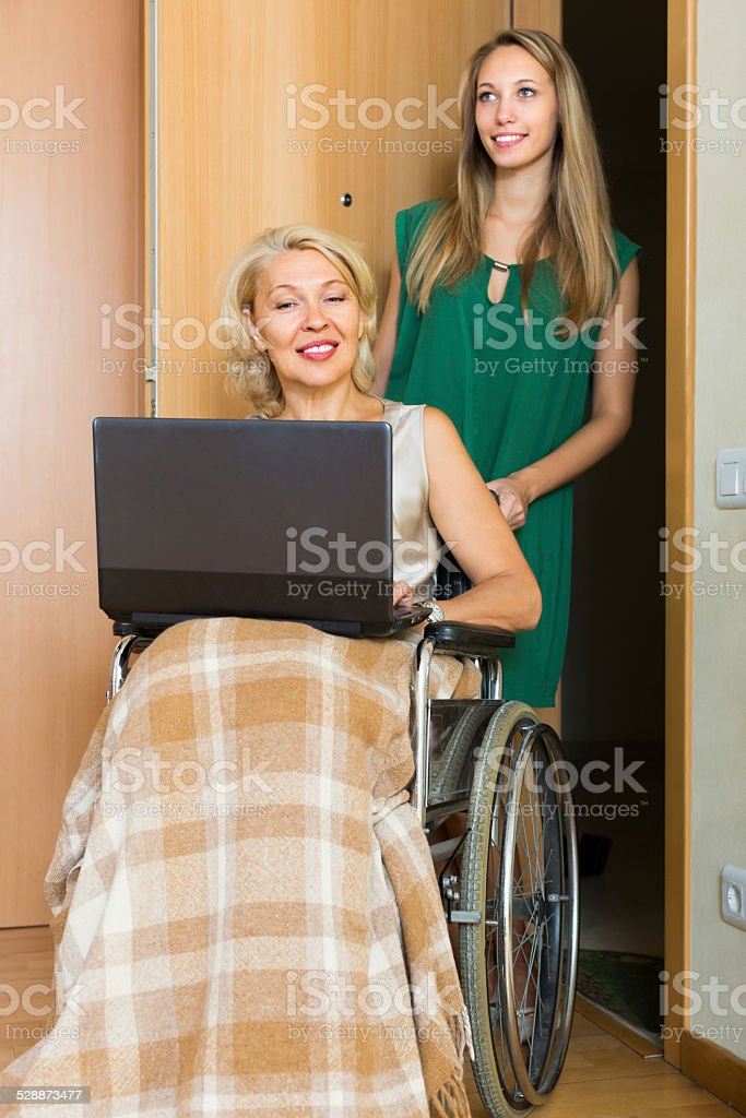 Social worker and invalid with laptop stock photo