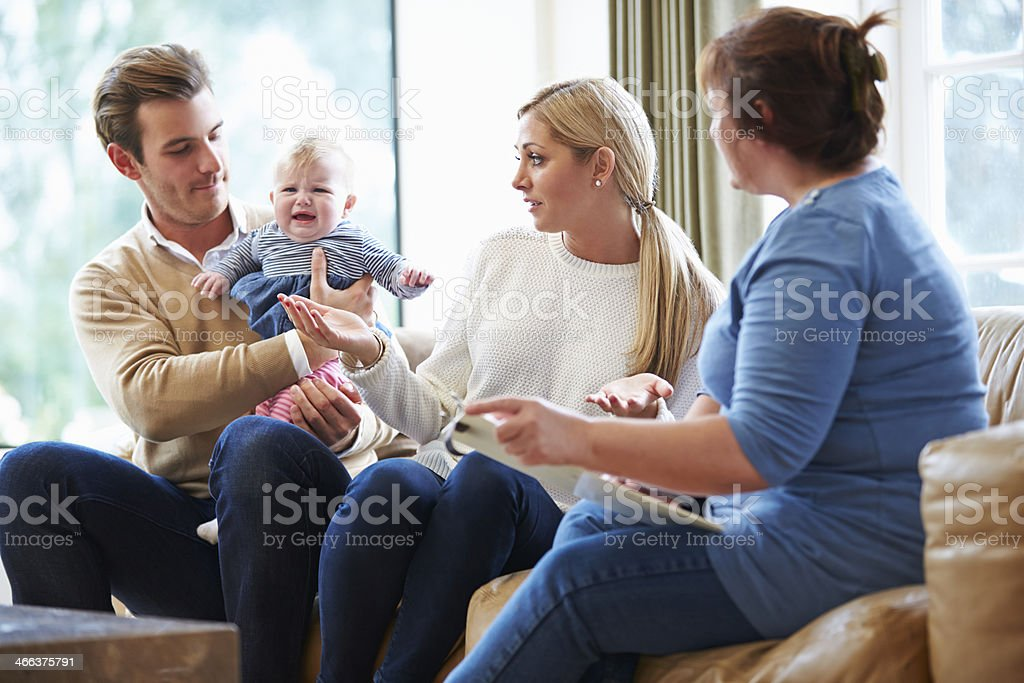 Social worker visiting couple with new adopted baby royalty-free stock photo