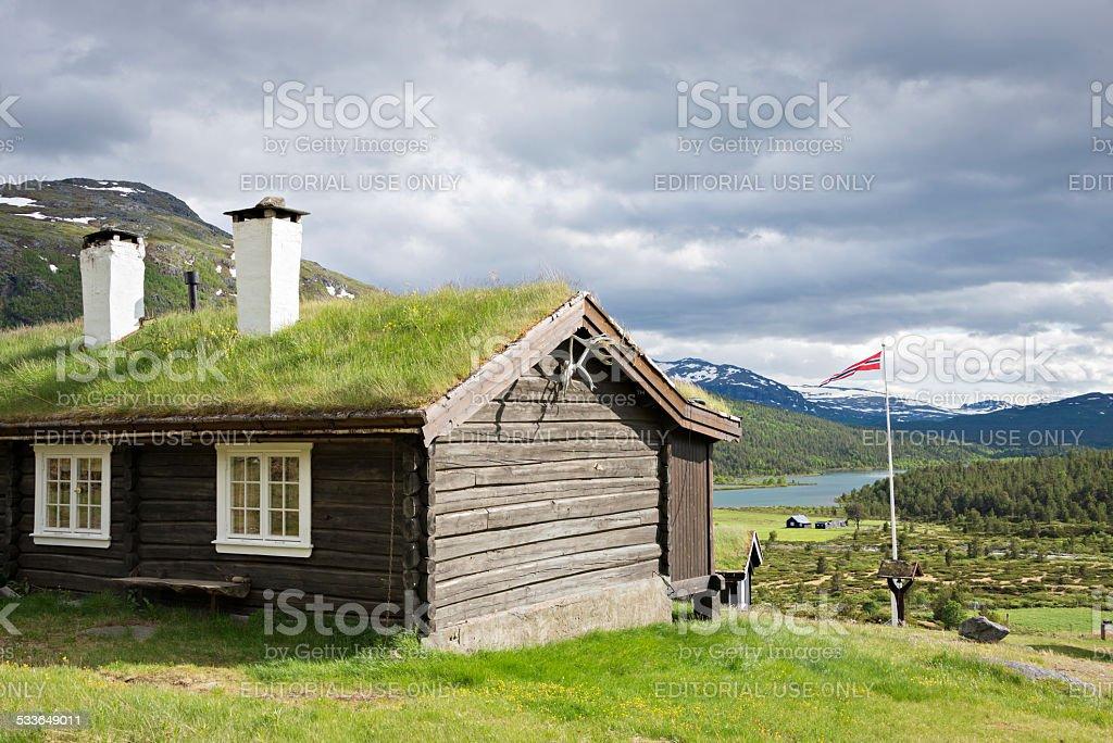 Sod roof log cabin under a dark gray sky stock photo