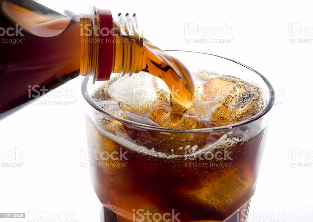 Soda (cola) being poured into plain glass with ice stock photo